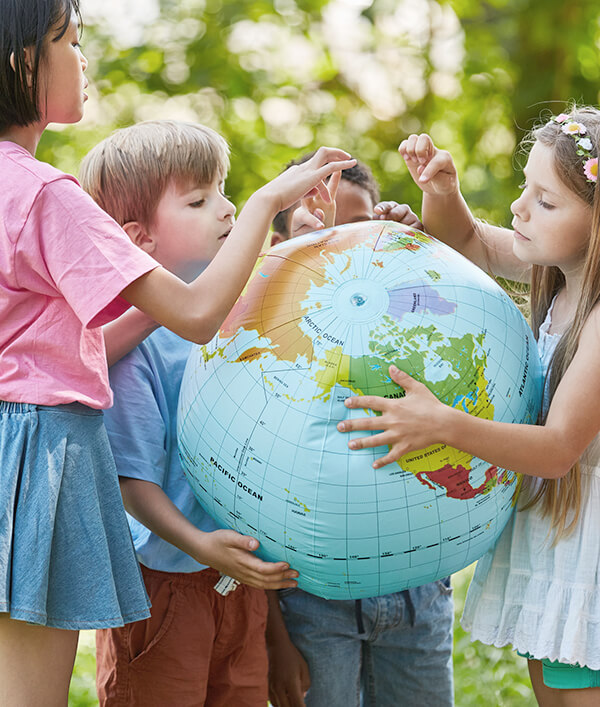 Dzieci uczą się przy pomocy globusa w Międzynarodowym Przedszkolu we Wrocławiu